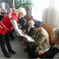 Керівник міськрайонної організації Товариства Червоного Хреста Баукова Г.М вручає чоловікам зимові чобітки та сорочки